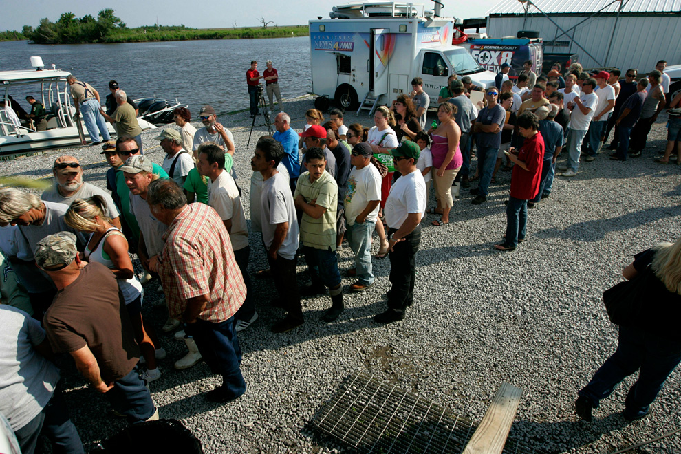 Unemployed commercial fishermen and their families wait in line to receive charity handouts in Hopedale, La.