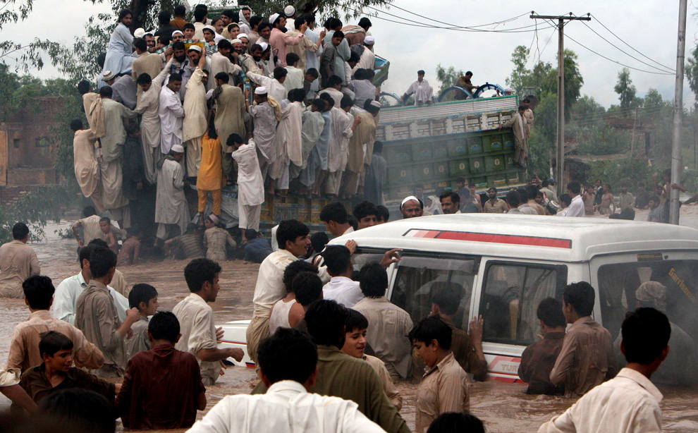Pakistani villagers move to high ground escaping a flood-hit village near Nowshera, Pakistan on Thursday, July 29, 2010. (AP Photo/Mohammad Sajjad)