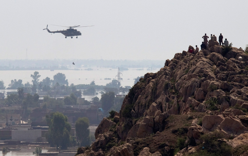 Residents watch from a nearby hill as army helicopters rescued trapped residents from Nowshera, Pakistan on July 31, 2010. (REUTERS/Adrees Latif)