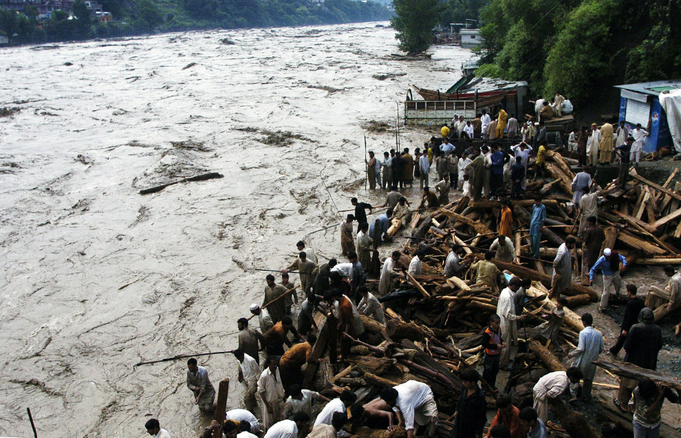 Residents stand by flood water that entered a residential area of Muzaffarabad, Pakistan on July 30, 2010. (SAJJAD QAYYUM/AFP/Getty Images)