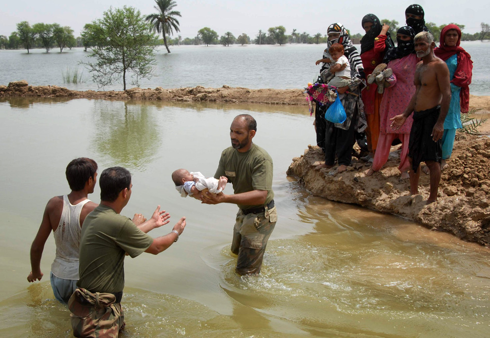Pakistan army soldiers pass a baby across a channel in the floodwater as they help people flee from their flooded village following heavy monsoon rains in Taunsa, Pakistan on Sunday, Aug. 1, 2010. (AP Photo/Khalid Tanveer)
