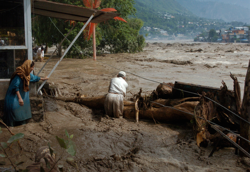 Villagers try to catch trees floating in the flooded Nelum river in Muzaffarabad, the capital of Pakistani Kashmir on Friday, July 30, 2010. (AP Photo/Aftab Ahmed)