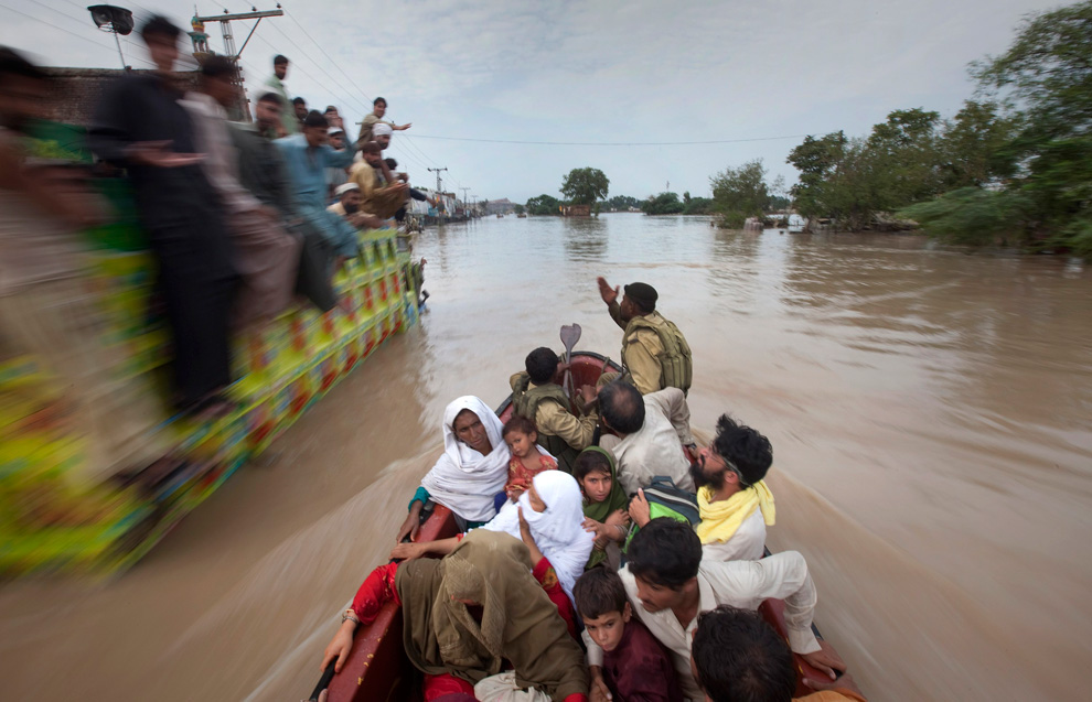 A family being rescued by army soldiers passes a cargo truck with men on top taking shelter from heavy floods in Nowshera, Pakistan on July 31, 2010. (REUTERS/Adrees Latif)