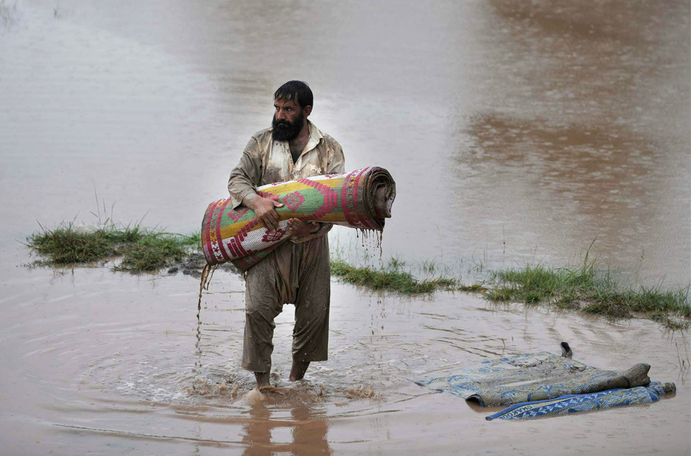 A flood survivor carries a soaked mat in a flooded area of Nowshera on August 3, 2010. (A Majeed/AFP/Getty Images)