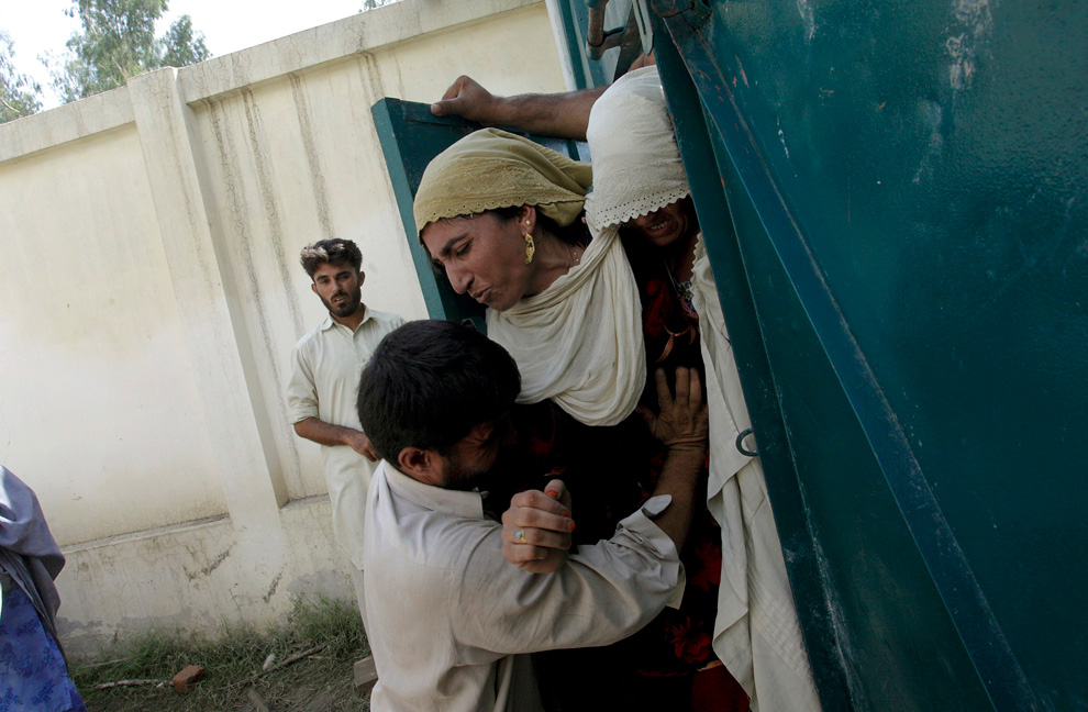 A Pakistani worker pushes back flood-stricken women who are trying to enter a relief center to get food supplies on the outskirts of Peshawar, Pakistan, Wednesday, Aug. 4, 2010. (AP Photo/Mohammad Sajjad)