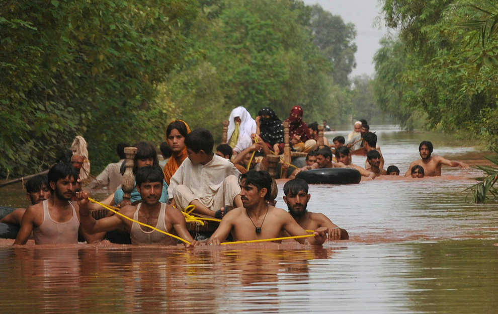 Residents evacuate to safety in a flood-hit area of Nowshera, Pakistan on July 30, 2010. (A. MAJEED/AFP/Getty Images)