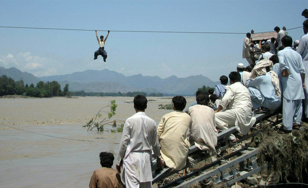 Onlookers perched on a damaged bridge watch a flood survivor use a rope to cross the river in Chakdara in Pakistan's Swat Valley on August 3, 2010. (STRDEL/AFP/Getty Images)