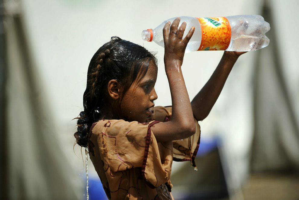 A young flood survivor cools herself with water at a makeshift camp in Nowshera, Pakistan on August 5, 2010. (FAROOQ NAEEM/AFP/Getty Images)