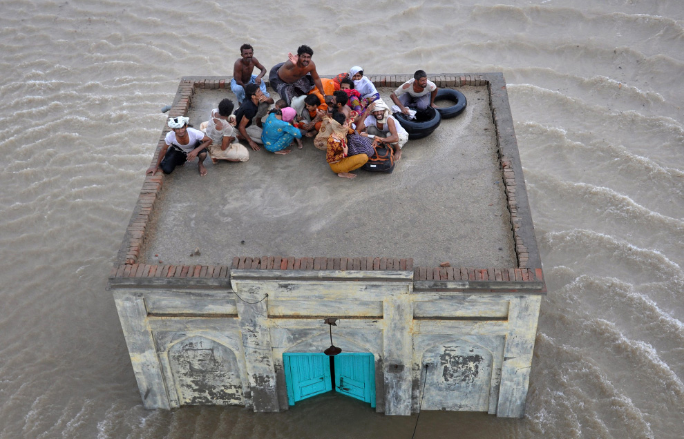 A family takes refuge on top of a mosque while awaiting rescue from flood waters in Sanawa, a town located in the Muzaffar Ghar district of Pakistan's Punjab province on August 5, 2010. (REUTERS/Stringer)
