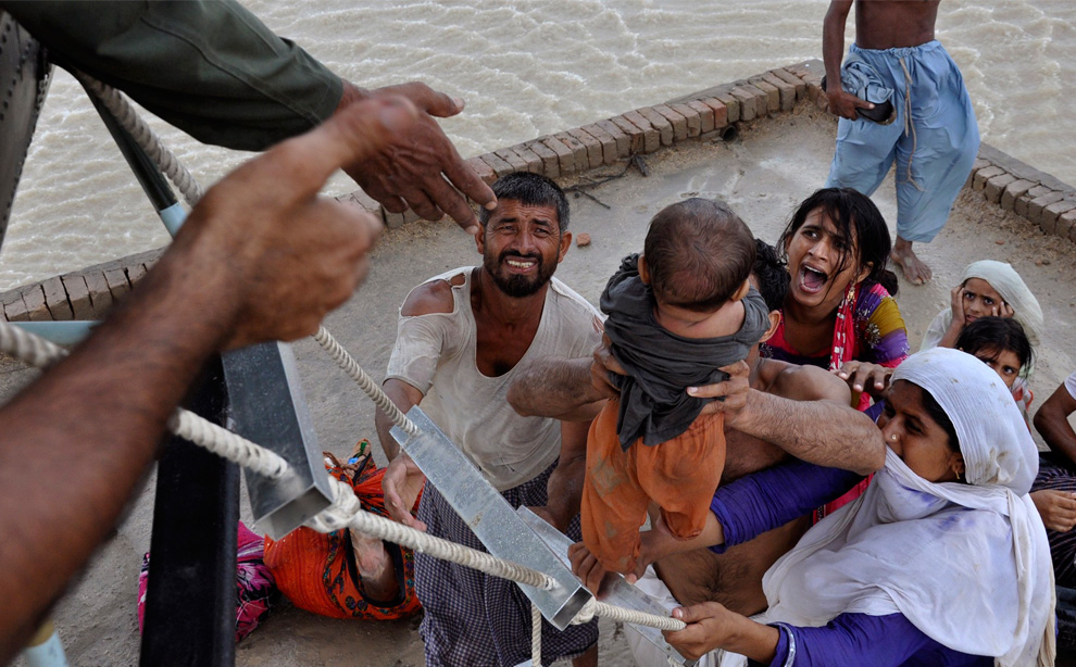 A woman yells as her child is evacuated from the roof of a mosque where residents were taking refuge from flood waters in Sanawa, Pakistan on August 5, 2010. (REUTERS/Stringer)