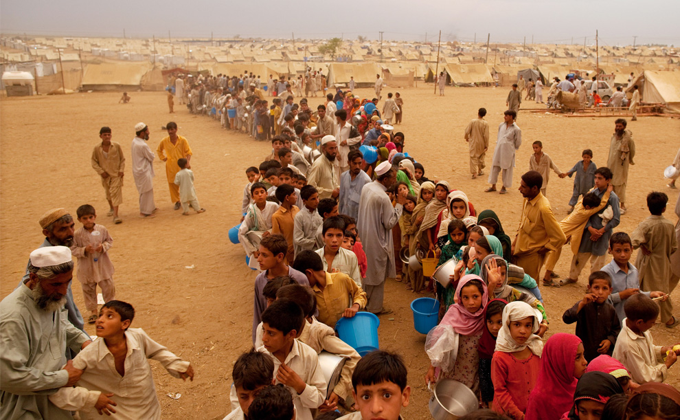 Children wait in line for food for hours at a camp in Swabi [Getty Images]