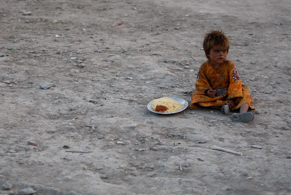 A child sits with a plate of food that was distributed as part of the holy month of Ramadan, at a refugee camp in Kabul, Afghanistan, on Saturday, Aug. 14, 2010. (AP Photo/Mustafa Quraishi)