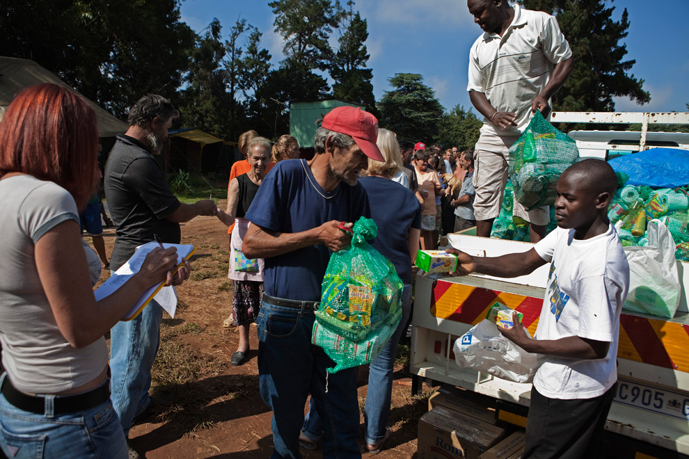 4 A man receives a monthly supply of food aid donated to residents of a squatter camp for poor white South Africans at Coronation Park in Krugersdorp on March 6, 2010. (REUTERS/Finbarr O'Reilly) # - Source: The Boston Globe
