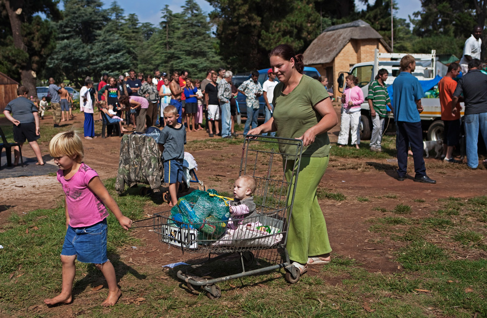 5 A woman pushes a cart with a monthly supply of donated food aid at Coronation Park in Krugersdorp, March 6, 2010. (REUTERS/Finbarr O'Reilly) # - Source: -  The Boston Globe