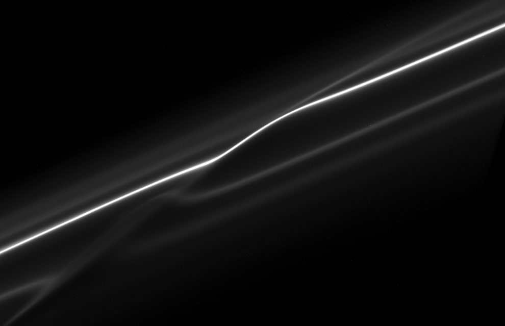 In this image of the F ring, taken shortly after its ring particles encountered the shepherd moon Prometheus, the disruption to the ring caused by the moon is evident. The bright core of the ring and its neighboring faint strands show kinks where the moon's gravity has altered the orbits of the ring particles. The image was taken on Oct. 23, 2008 at a distance of approximately 444,000 km (276,000 mi) from Saturn. Image scale is 2 km (1 mile) per pixel. (NASA/JPL/SSI)