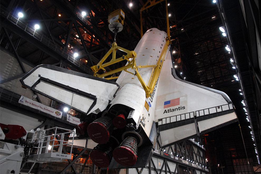 Блок сборки аппарата в Космическом центре имени Кеннеди во Флориде, кран поднимает Атлантис в вертикальное положение. Шаттл установили в высокий отсек 3, где к нему был прикреплен внешний топливный бак и твердотопливные ракетные ускорители на подвижной пусковой платформе. (NASA/Cory Huston)