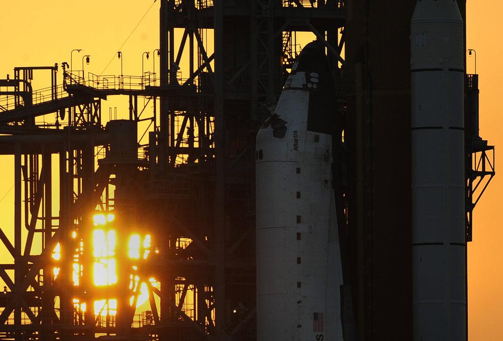 Солнце садится за космическим кораблем Атлантис. 10 мая 2009 года, Космический центр Кеннеди во Флориде, за один день до старта. (STAN HONDA/AFP/Getty Images)