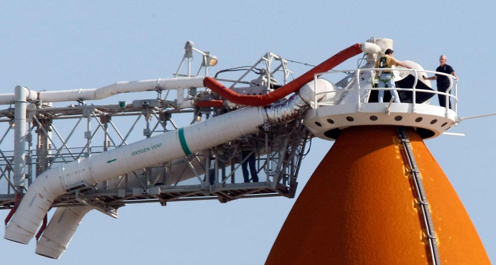 Специалисты NASA стоят на верхней части внешних топливных баков шаттла «Атлантис», установленного на стартовой площадке 39-А в Kennedy Space Center. 10 мая 2009 года на Мысе Канаверал, штат Флорида. (Joe Raedle/Getty Images)