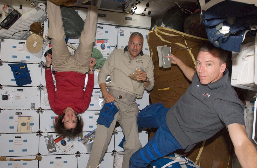 Космонавты Меган МакАртур, Майкл Массимино (в центре) и Эндрю Фойстел во время миссии шаттла «Атлантис» STS-125, перед обедом на орбите Земли. (NASA)