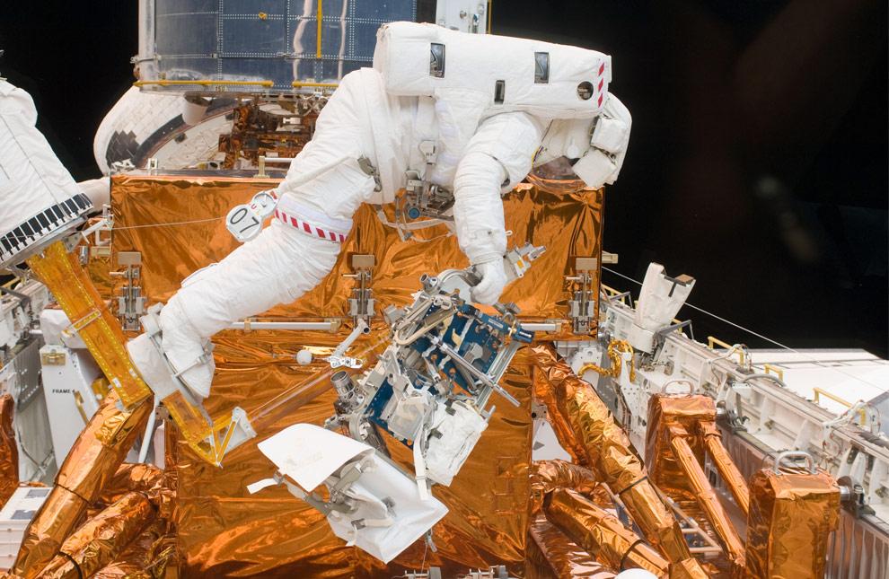 Астронавт Майкл Гуд работает с помощью одного из комплектов инструментов, которые созданы специально для ремонта  телескопа Хаббл в грузовом отсеке шаттла «Атлантис». (NASA)