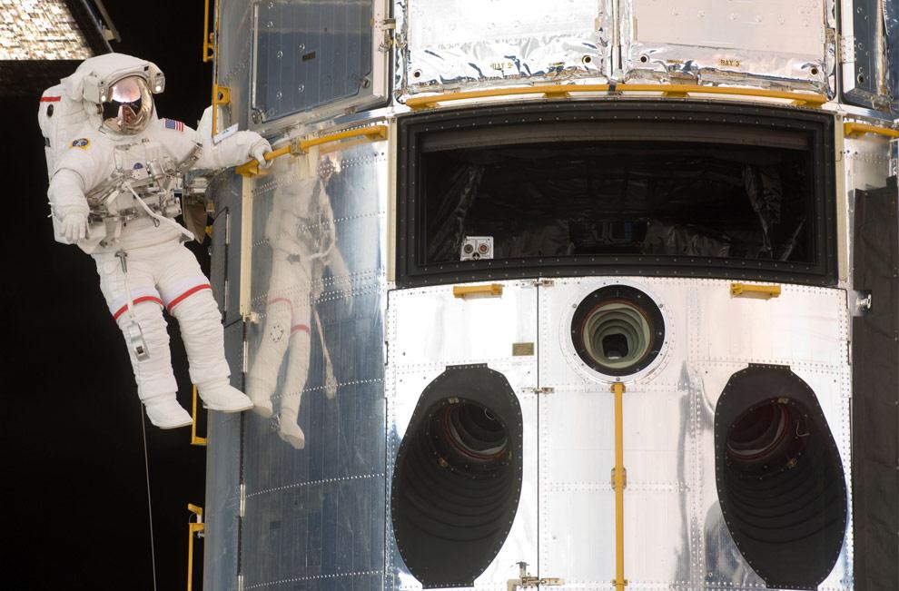 Астронавт Джон Грунсфелд держится за поручни во время выполнения работ по ремонту телескопа Хаббл 14 мая 2009. Грунсфелд, астронавт-ветеран, которого много связывает с телескопом, будет участвовать в двух из оставшихся четырех выходов в открытый космос. (NASA)