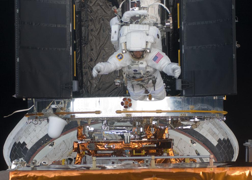 Астронавт Эндрю Фойстел, специалист миссии STS-125, на ограничителе для ног, находящемся в конце манипуляторной системе Атлантиса участвует в работах по переоснащению и модернизации телескопа Хаббл в открытом космосе. (NASA)