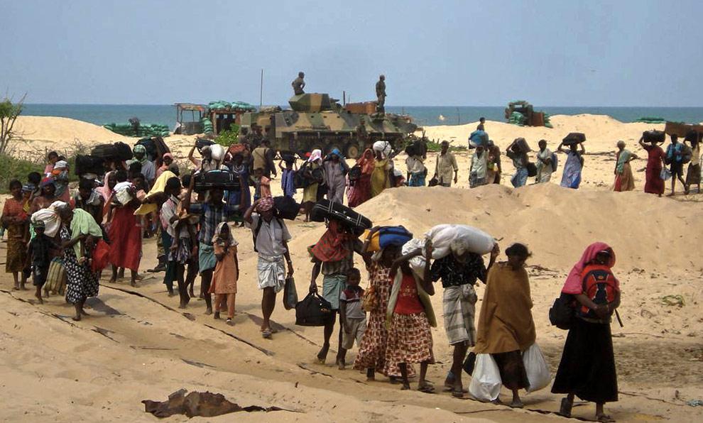 На этом фото, предоставленном шриланкийской армией, можно видеть мирных жителей, которые спешно покидают регион в северо-восточной части острова все еще находящийся под контролем Тамильских тигров. 21 апреля 2009. (AFP/AFP/Getty Images)