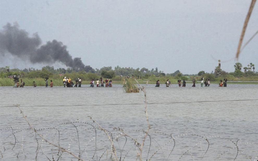 На этом фото, предоставленном шриланкийской армией, этнические тамилы спешно покидают районы контролируемые тамильскими тиграми. По словам представителей армии, беженцы направляются к городу Путуматталан, расположенному к северо-востоку от столицы страны Коломбо. (AP Photo/Sri Lankan Army)