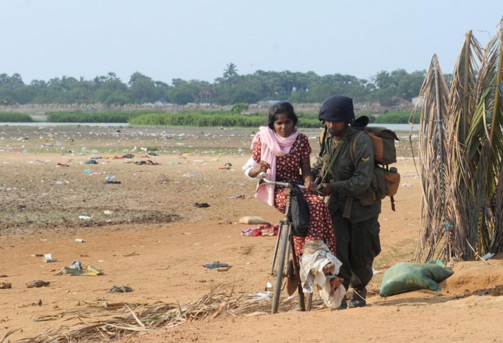 Шриланкийский солдат везет женщину на велосипеде через поле усыпанное брошенными скарбом. Недалеко от города Путуматталан, на севере Шри-Ланки 22 апреля 2009 после того, как местные жители покинули этот район, который все еще находится под контролем организации Тигры освобождения Тамил Илама (ТОТИ ) в зоне запрещения ведения огня. (REUTERS/Stringer)
