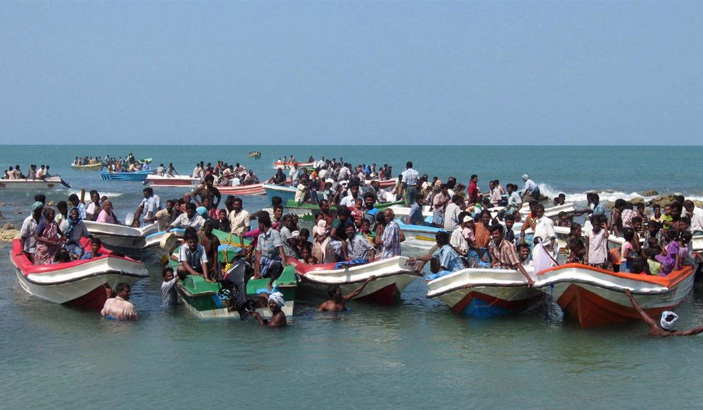 Это фото, предоставленное шриланкийским флотом 21 апреля 2009 года, доказывает то, что утверждают военные: тысячи людей на лодках, покидают регион на северо-востоке Шри-Ланки, находящийся под контролем тамильских тигров. Уже прошло три дня с тех пор, как  войска Шри-Ланки разрушили построенные повстанцами оборонительные заграждения - длинную земляную стену вдоль прибрежной полосы, что дало возможность мирным жителям бежать. В лагерях беженцев уже находится 81.420 человек. (REUTERS/Sri Lankan Government)