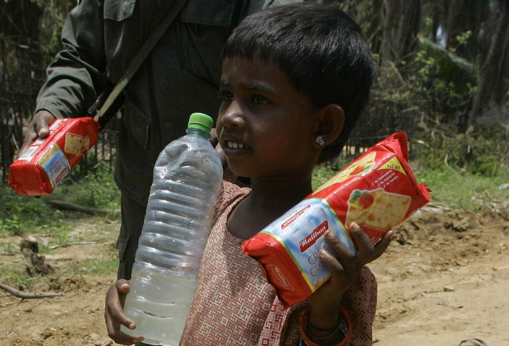 Тамильская девочка, которая недавно прибыла в зону, контролируемую правительством, идет с бутылкой воды и упаковкой печенья в руках. Регион, находящийся вблизи зоны военных действий в Путуматталан в Puthukudiyiruppu, около 240 километров (150 миль) к северо-востоку от столицы Шри-Ланки, Коломбо, в пятницу, 24 апреля 2009. (AP Photo/ Eranga Jayawardena)