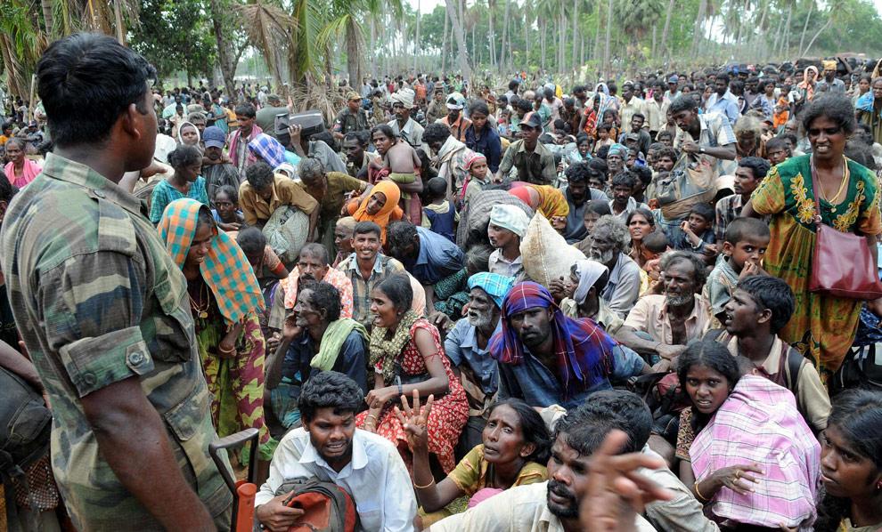 Солдат правительственных войск смотрит на толпу гражданских, которые прибыли в Путуматталан в Puthukudiyiruppu, на севере Шри-Ланки 24 апреля 2009 после того, как бежали из региона, который все еще находится под контролем организации сепаратистов. (REUTERS/Stringer)