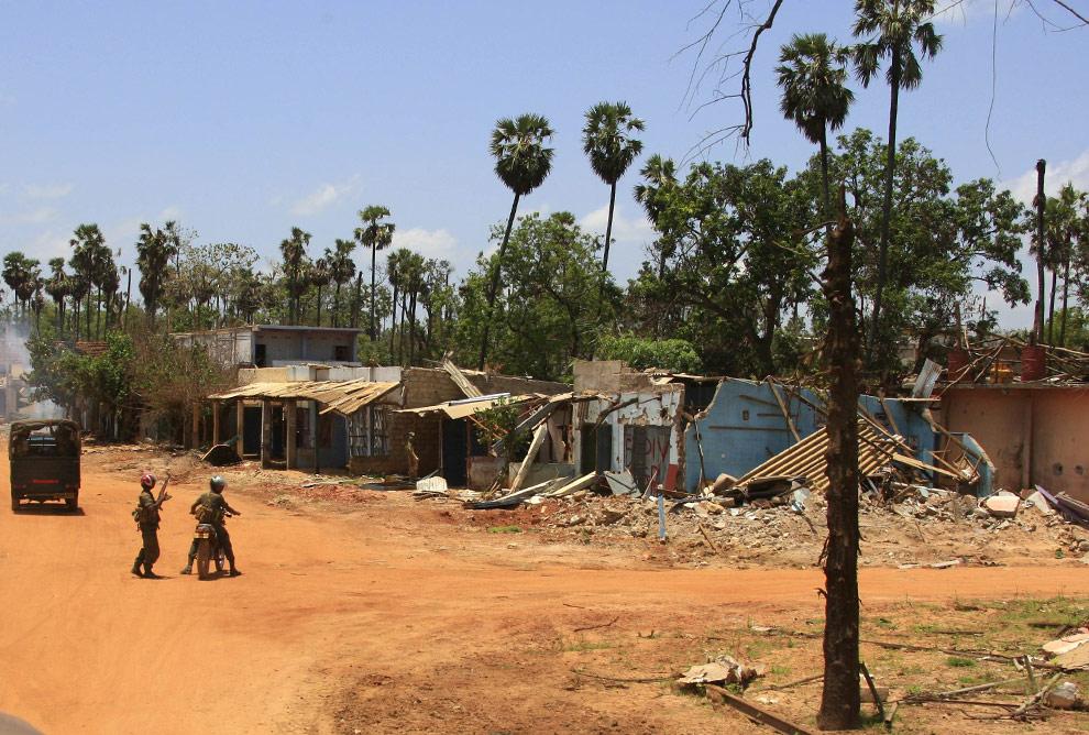 Солдаты правительственных войск Шри-Ланки на фоне разрушенных зданий в городе Путуматталан недалеко от зоны запрещения ведения огня на севере Шри-Ланки 24 апреля 2009. (REUTERS/David Gray)