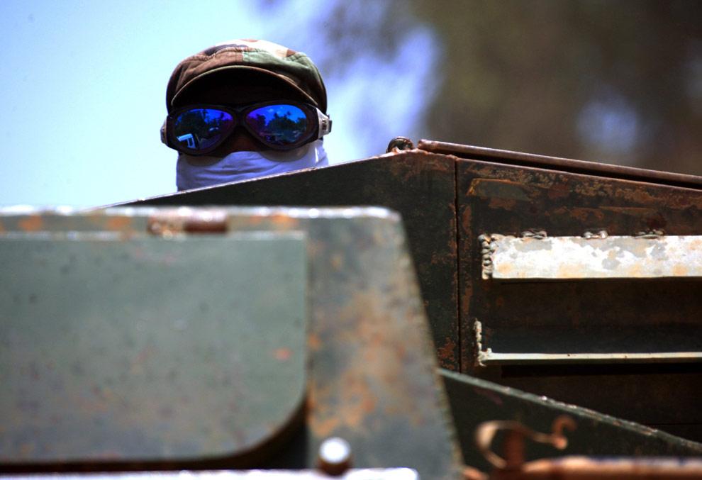 Солдат правительственных войск Шри-Ланки в маске и защитных очках едет в бронированной транспорте по окраине города, расположенного вблизи Путуматталана, в  зоне запрещения ведения огня в северной части Шри-Ланки 24 апреля 2009. (REUTERS/David Gray)
