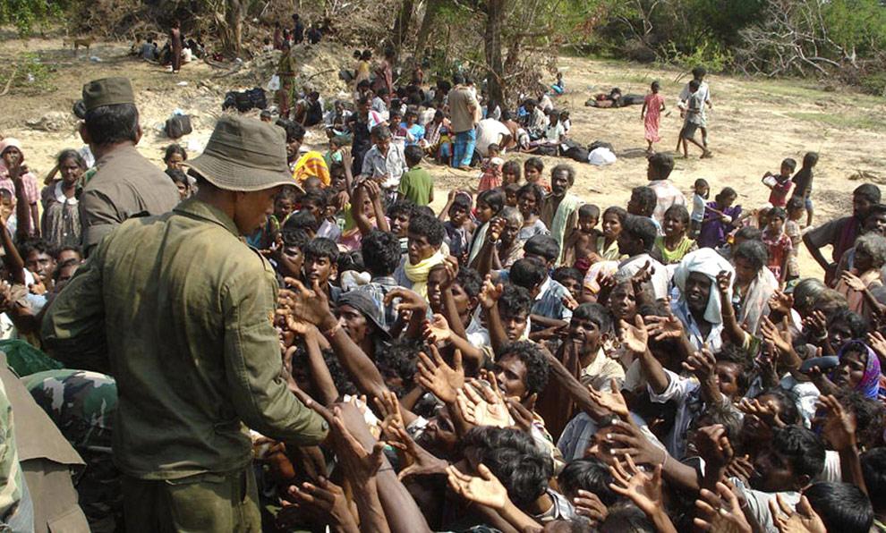 На этом недатированном фото, предоставленном шриланкийской армией в среду, 22 апреля 2009, солдат правительственных войск распределяет продовольственные посылки среди этнических тамилов, которые бежали из районов, контролируемых тамильскими тиграми. (AP Photo/Sri Lankan Army)