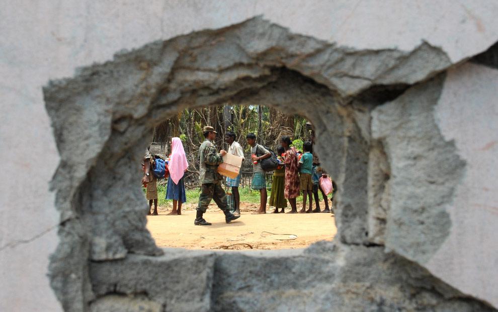 В отверстие от снаряда видно, как шриланкийский солдат несет коробку с  продовольственными пайками, предназначенными для беженцев-тамилов. Путуматталан, 24 апреля 2009. (PEDRO UGARTE/AFP/Getty Images)