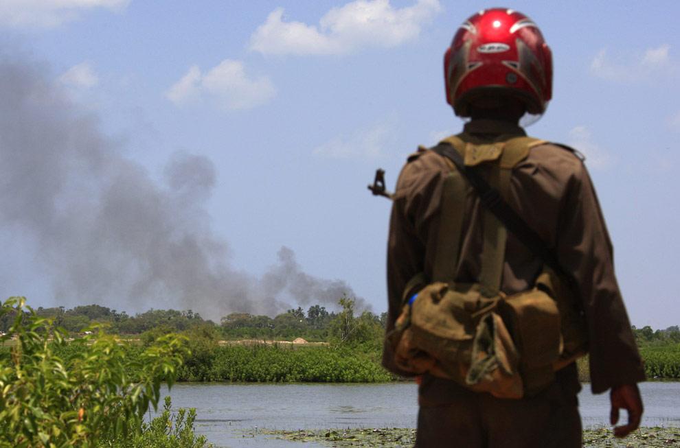 Шриланкийский солдат смотрит на столб дыма, поднимающийся над территорией зоны запрещения ведения огня недалеко от города Путуматталана, в северной части Шри-Ланки 24 апреля 2009. (REUTERS/David Gray)