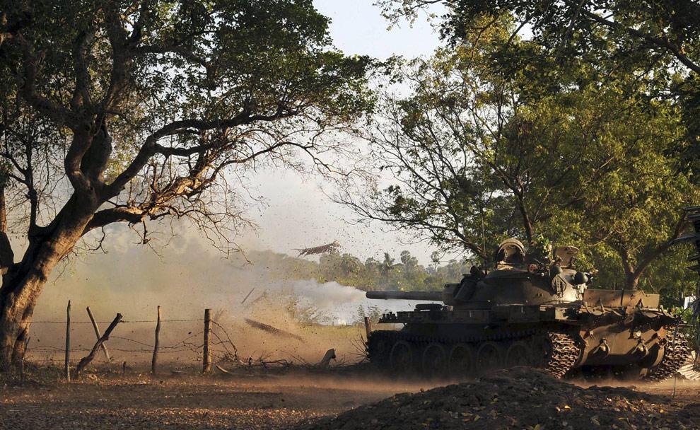 Танк шриланкийской правительственной армии стреляет в направлении Муллаитиву, где продолжаются бои между армией Шри-Ланки и тамильскими сепаратистами. 24 марта, 2009. (REUTERS/Stringer)