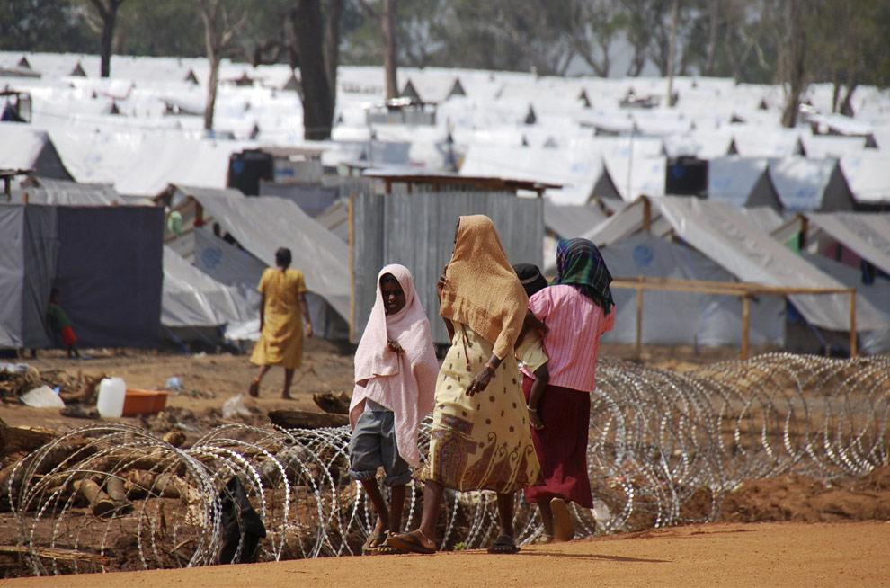 Тамильские женщины с детьми идут рядом с колючей проволокой в лагере беженцев, в котором находятся тамилы, бежавшие из зоны боевых действий, в Вавунии, в 254 км (158 милях) к северу от Коломбо, 4 апреля 2009. (REUTERS/ Stringer)