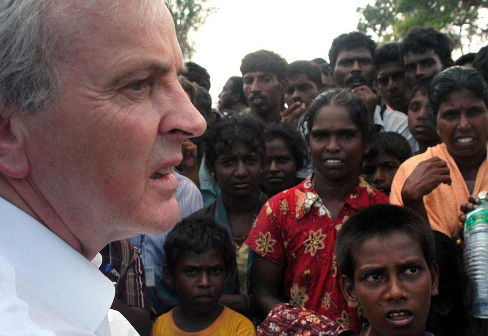 Заместитель Генерального секретаря ООН по гуманитарным вопроса Джон Холмс общается с гражданскими во время своего визита в лагерь беженцев, расположенный недалеко от города Маник в северной части Шри-Ланки. 27 апреля 2009. (REUTERS/United Nations)