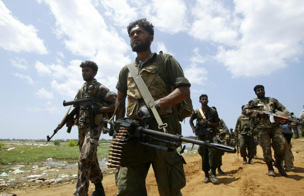 Шриланкийские солдаты приближаются к зоне военных действий Путуматталана в Puthukudiyiruppu, в 240 километрах (150 миль) к северо-востоку от Коломбо, 24 апреля 2009. (AP Photo/ Eranga Jayawardena)