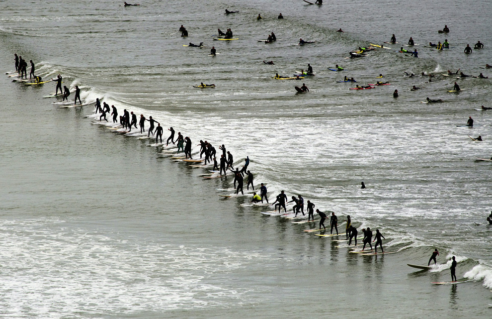 Surfers ride a wave in the annual Earthwave event, where the participating surfers try to break the Guinness World Record for the number of surfers surfing a single wave on September 26, 2010 at the Muizemberg beach, Cape Town, South Africa. Unconfirmed reports are that 95 surfers simultaneously rode a wave together, not enough to break the record of 103, set the previous year, at the same beach. (RODGER BOSCH/AFP)