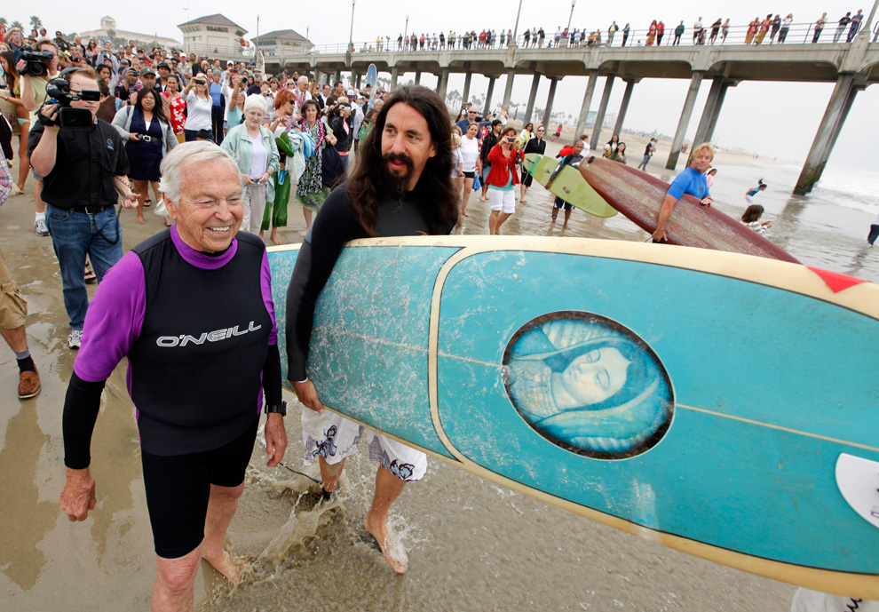 Reverend Matt Munoz (center) heads to the surf with Reverend Christian Mondor (left) during the Blessing of the Waves ceremony at the pier in Huntington Beach, California on Sunday, Oct. 3,2010. Hundreds of Californians joined surfing priests and religious leaders from multiple faiths Sunday to honor the ocean and protest coastal pollution. (AP Photo/Richard Vogel)