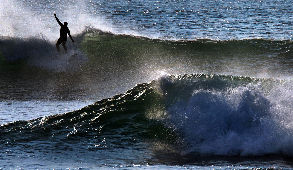 Along the coast near Scituate, Massachusetts, a surfer rides a wave in the early morning on September 4th, 2010. (Boston Globe/David L Ryan)