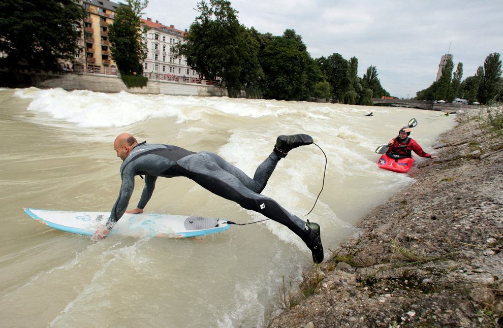 A surfer jumps into the Isar river with his board on July 28, 2010 in Munich, Germany. After heavy rainfall the Isar river carries plenty of water and forms a stationary wave. (Miguel Villagran)