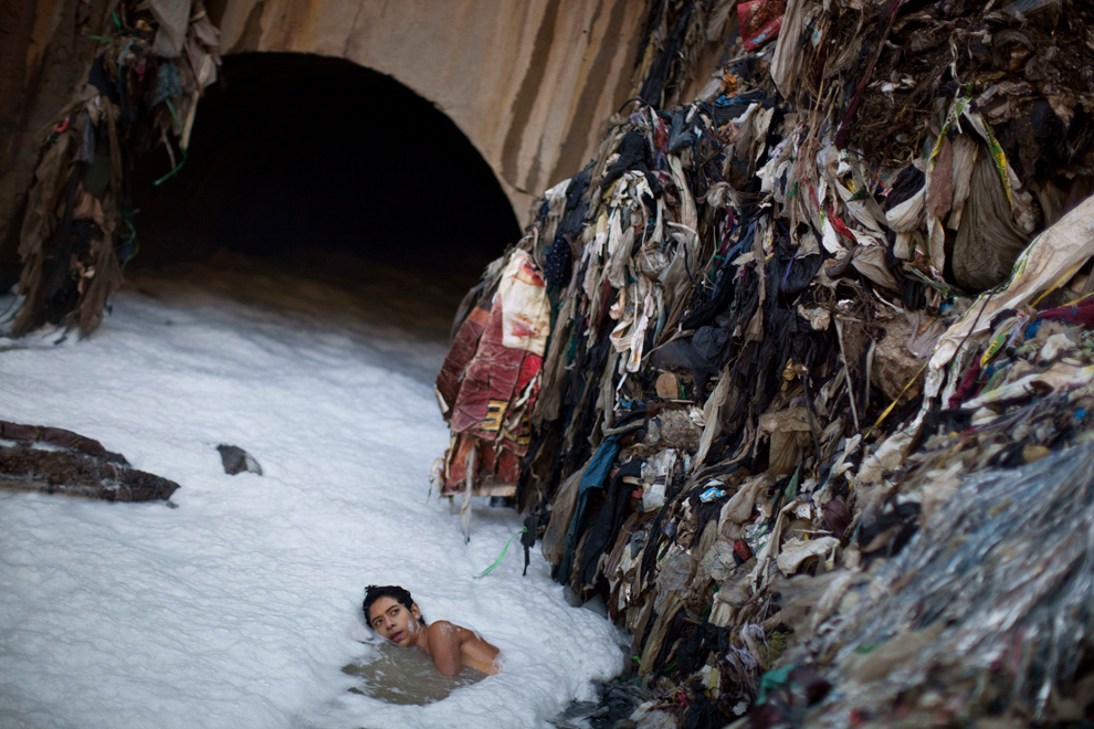 A young man who goes by the name Paleta searches for metal in contaminated water by a tunnel where the water from sewage converges with storm water runoff. (Rodrigo Abd/Associated Press)