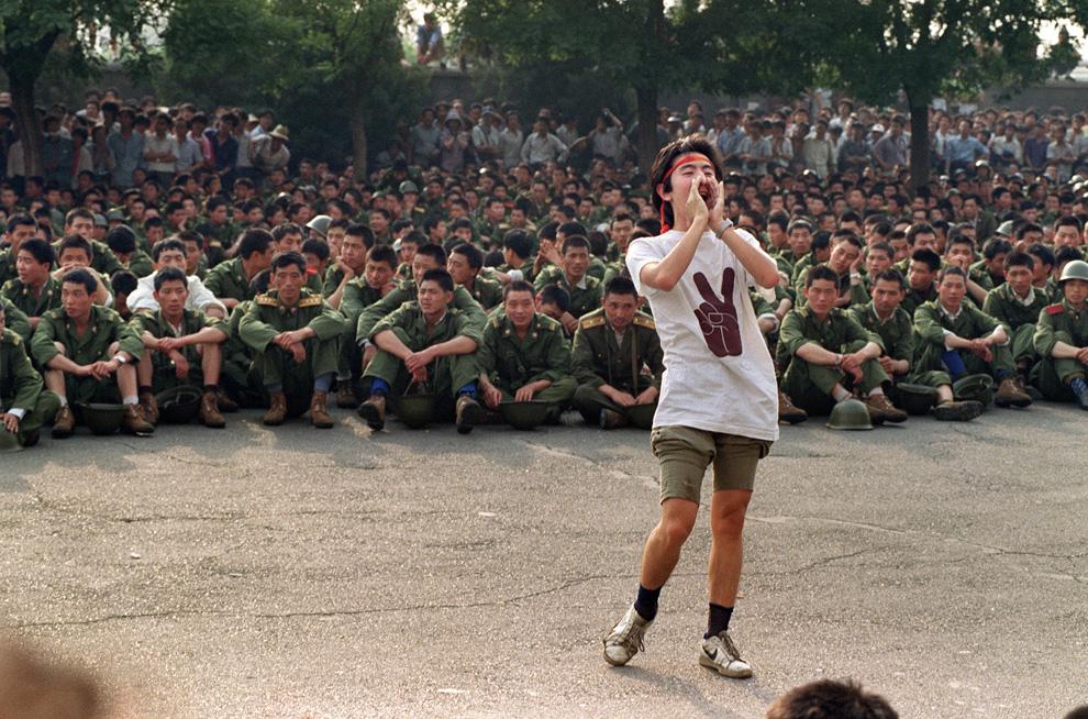 На этом архивном фото, сделанном 3 июня 1989 на заполненной людьми центральной площади Пекина студент-диссидент просит солдат вернуться домой. (CATHERINE HENRIETTE/AFP/Getty Images)