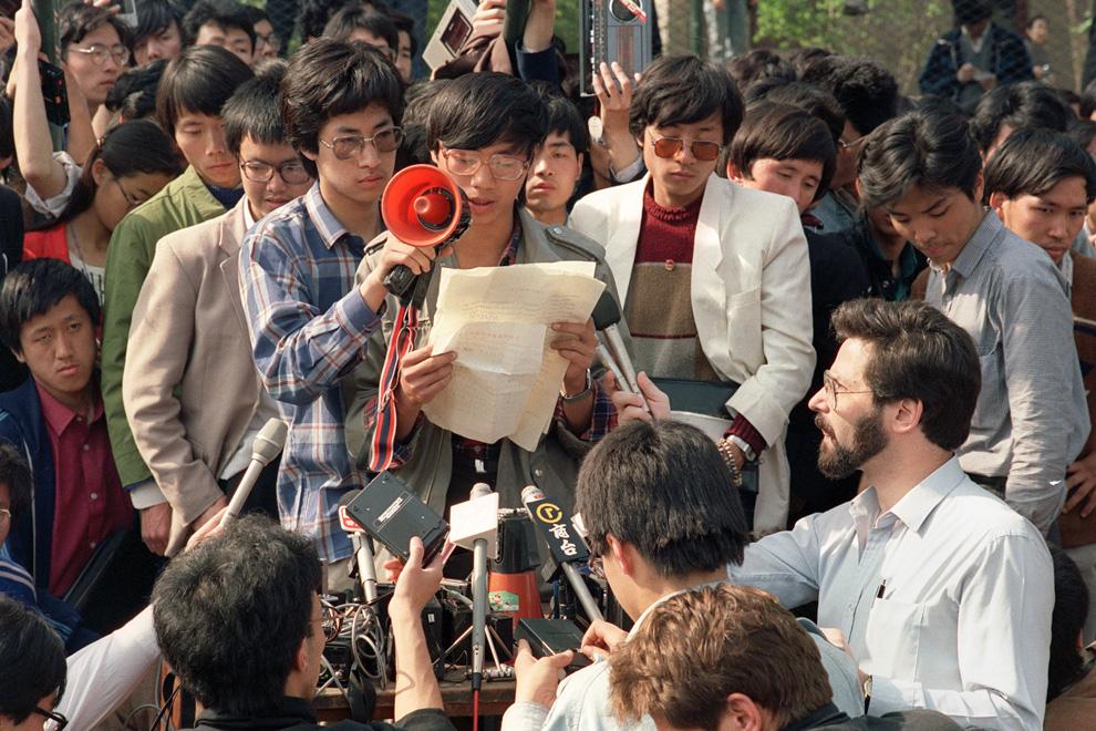 На этом фото, сделанном 1 мая 1989, Ван Дан (в центре), ведущий китайский диссидент и член делегации Совета студентов Пекинского университета, обращается к иностранным корреспондентам во время демократических демонстраций на площади Тяньаньмэнь. (CATHERINE HENRIETTE/AFP/Getty Images)