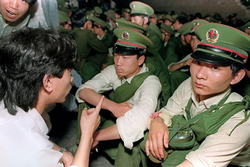 На этом архивном фото, сделанном 3 июня 1989 студент-диссидент (слева) кричит солдатам, чтобы они возвращались домой, в то время как толпа продолжает наводнять центр Пекина перед началом подавления армией продемократической демонстрации. (CATHERINE HENRIETTE/AFP/Getty Images)