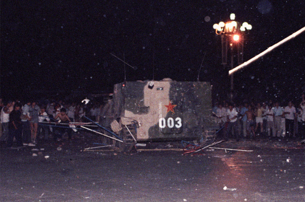 Броневик сносит одну из палаток установленных протестующими на площади Тяньаньмэнь рано утром в воскресенье, 4 июня 1989. (REUTERS/Stringer)